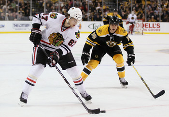 BOSTON, MA - MARCH 29:  Michael Frolik #67 of the Chicago Blackhawks heads for the net as Nathan Horton #18 of the Boston Bruins defends on March 29, 2011 at the TD Garden in Boston, Massachusetts.  (Photo by Elsa/Getty Images)