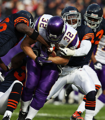 CHICAGO - NOVEMBER 14: Toby Gerhart #32 of the Minnesota Vikings is tackled by (L-R) Tim Jennings #26, Danieal Manning #38 and Chris Harris #46 of the Chicago Bears at Soldier Field on November 14, 2010 in Chicago, Illinois. The Bears defeated the Vikings