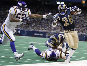 ST. LOUIS, MO - NOVEMBER 30:  Marshall Faulk #28 of the St. Louis Rams is shoved out of bounds by Henri Crockett #52 of the Minnesota Vikings on November 30, 2003 at the Edward Jones Dome in St. Louis, Missouri. The Rams defeated the Vikings 48-17.  (Phot
