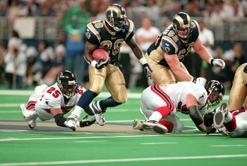 15 Oct 2000:  Marshall Faulk #28 of the St. Louis Rams dodges a tackle by the Atlanta Falcons at the TransWorld Dome in St. Louis, Missouri. The Rams won 45-29.Mandatory Credit: Jeff Gross/Allsport
