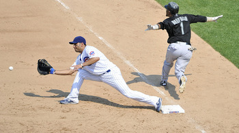 CHICAGO, IL - JULY 17:  Emilio Bonifacio #1 of the Florida Marlins (R) reaches first base on an infield hit as first baseman Carlos Pena #22 of the Chicago Cubs reaches for the throw during the eighth inning at Wrigley Field on July 17, 2011 in Chicago, I