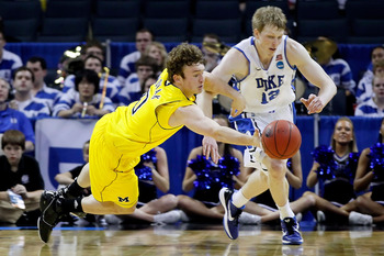 CHARLOTTE, NC - MARCH 20:  Zack Novak #0 of the Michigan Wolverines dives for the ball alongside Kyle Singler #12 of the Duke Blue Devils in the first half during the third round of the 2011 NCAA men's basketball tournament at Time Warner Cable Arena on M