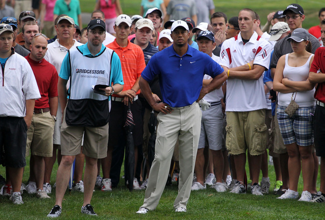 AKRON, OH - AUGUST 06:  Tiger Woods (R) and caddie Byron Bell (L) look on from the fourth hole during the third round of the World Golf Championships-Bridgestone Invitational on the South Course at Firestone Country Club on August 6, 2011 in Akron, Ohio.