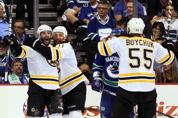 VANCOUVER, BC - JUNE 15:  Patrice Bergeron #37 of the Boston Bruins celebrates with Gregory Campbell #11 and Johnny Boychuk #55 after he scored the 3rd goal in the second period against Roberto Luongo #1 of the Vancouver Canucks during Game Seven of the 2
