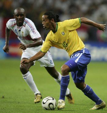 FRANKFURT, GERMANY - JULY 1:  Ronaldinho of Brazil is pursued by Patrick Vieira of France during the FIFA World Cup Germany 2006 Quarter-final match between Brazil and France at the Stadium Frankfurt on July 1, 2006 in Frankfurt, Germany.  (Photo by Ben R