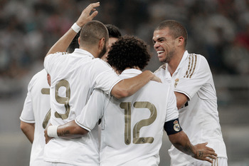 TIANJIN, CHINA - AUGUST 06:  Karim Benzema #9 of Real Madrid celebrates a goal with team-mates during the pre-season friendly match between Tianjin Teda and Real Madrid at Water Drop Stadium on August 6, 2011 in Tianjin, China. (Photo by Lintao Zhang/Gett