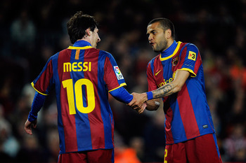 BARCELONA, SPAIN - FEBRUARY 20:  Goalscorer Lionel Messi (L) of of FC Barcelona is congratulated by team-mate Dani Alves during the La Liga match between FC Barcelona and Athletic Bilbao at Camp Nou on February 20, 2011 in Barcelona, Spain. Barcelona won