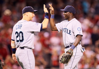 ANAHEIM, CA - AUGUST 6:  Trayvon Robinson #12 and Mike Carp #20 of the Seattle Mariners celebrate after the game with the Los Angeles Angels of Anaheim on August 6, 2011 at Angel Stadium in Anaheim, California.  The Mariniers won 5-1.  (Photo by Stephen D