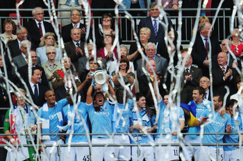 LONDON, ENGLAND - MAY 14:  Carlos Tevez lifts the trophy after he and his Manchester City team mates won the FA Cup sponsored by E.ON Final match between Manchester City and Stoke City at Wembley Stadium on May 14, 2011 in London, England.  (Photo by Shau