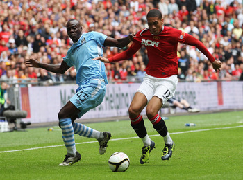 LONDON, ENGLAND - AUGUST 07:  Mario Balotelli of Manchester City and Chris Smalling of Manchester United battle for the ball during the FA Community Shield match sponsored by McDonald's between Manchester City and Manchester United at Wembley Stadium on A