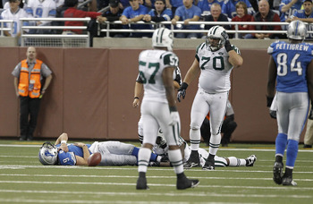 DETROIT - NOVEMBER 07: Matthew Stafford #9 of the Detroit Lions lays on the ground holding his right shoulder after being sacked by Bryan Thomas #58 of the New York Jets during the third quarter of the game at Ford Field on November 7, 2010 in Detroit, Mi