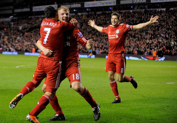 LIVERPOOL, ENGLAND - FEBRUARY 02:  Luis Suarez of Liverpool celebrates with team mates Dirk Kuyt and Steven Gerrard (R) after scoring his team's second goal during the Barclays Premier League match between Liverpool and Stoke City at Anfield on February 2