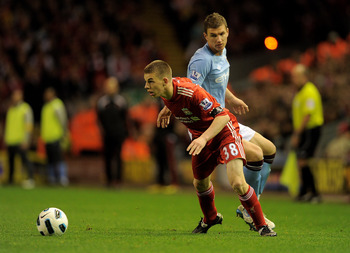 LIVERPOOL, ENGLAND - APRIL 11:   John Flanagan of Liverpool competes with Edin Dzeko of Manchester City during the Barclays Premier League match between Liverpool and Manchester City at Anfield on April 11, 2011 in Liverpool, England. (Photo by Michael Re