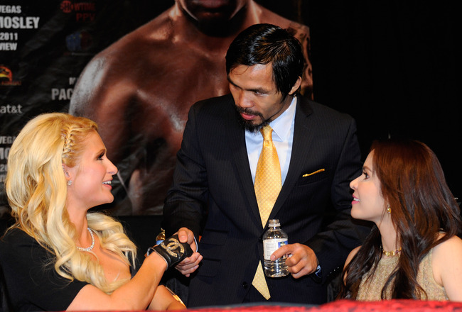 LAS VEGAS, NV - MAY 07:  (L-R) Paris Hilton shakes hands with Manny Pacquiao as Hilton sits with Jinkee Pacquiao during the post-fight news conference after Pacquiao defeated Shane Mosley by unanimous decision in the WBO welterweight title fight at MGM Gr
