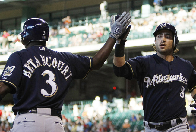 HOUSTON - AUGUST 05:  Ryan Braun #8 of the Milwaukee Brewers receives a high five from Yuniesky Bentancourt #3 after scoring in the firt inning against the Houston Astros at Minute Maid Park on August 5, 2011 in Houston, Texas.  (Photo by Bob Levey/Getty