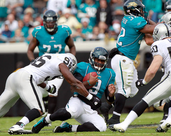 JACKSONVILLE, FL - DECEMBER 12: Quarterback David Garrard #9 of the Jacksonville Jaguars slides while being tackled by Kameron Wimbley #96 of the Oaklland Raiders during the game at EverBank Field on December 12, 2010 in Jacksonville, Florida.  (Photo by