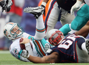 FOXBORO, MA - JANUARY 02:  Chad Henne #7 of the Miami Dolphins is brought down in the first half by Jerod Mayo #51 and Landon Cohen #66 of the New England Patriots on January 2, 2011 at Gillette Stadium in Foxboro, Massachusetts.  (Photo by Elsa/Getty Ima