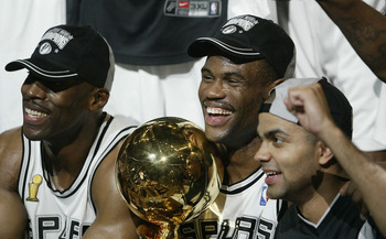 SAN ANTONIO - JUNE 15:  David Robinson #50, Kevin Willis #42 and Tony Parker #9 of the San Antonio Spurs celebrate with the championship trophy after defeating the New Jersey Nets 88-77 during game six of the 2003 NBA Finals on June 15, 2003 at the SBC Ce