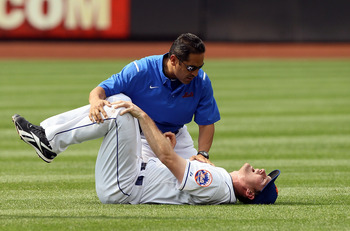 NEW YORK, NY - AUGUST 07:  Daniel Murphy #28 of the New York Mets is tended to by head trainer Ray Ramirez after being injured after Jose Constanza #17 (not pictured) of the Atlanta Braves stole second base in the seventh inning at Citi Field on August 7,