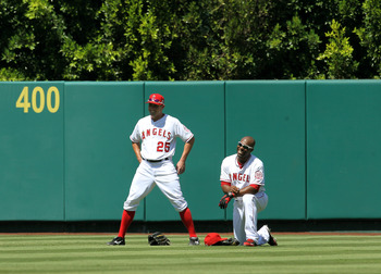 ANAHEIM, CA - AUGUST 7:  Center fielder Peter Bourjos #25 and right fielder Torii Hunter #48 of the Los Angeles Angels of Anaheim relax in the outfield during a pitching change in the ninth inning against he Seattle Mariners on August 7, 2011 at Angel Sta
