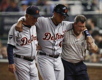 KANSAS CITY, MO - AUGUST 06: Victor Martinez #41 of the Detroit Tigers is helped off the field by manager Jim Leyland #10 and a team trainer after he was injured while trying to score in the eighth inning at Kauffman Stadium on August 6, 2011 in Kansas Ci