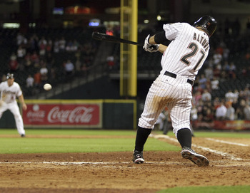 HOUSTON - AUGUST 01:  Jose Altuve #27 of the Houston Astros drives the ball up the middle for a fielders choice in the 10th inning scoring Humberto Quintero #51 from third base after the throw to home could not be handled by catcher Ryan Hanigan #29 at Mi