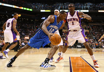 PHOENIX - DECEMBER 11:  Dwight Howard #12 of the Orlando Magic drives the ball against Amar'e Stoudemire #1 of the Phoenix Suns during the NBA game at US Airways Center on December 11, 2009 in Phoenix, Arizona. NOTE TO USER: User expressly acknowledges an