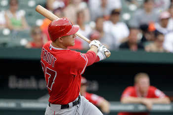 BALTIMORE, MD - JULY 24: Mike Trout #27 of the Los Angeles Angels of Anaheim follows his three RBI home run against the Baltimore Orioles during the eighth inning at Oriole Park at Camden Yards on July 24, 2011 in Baltimore, Maryland. The Angels defeated