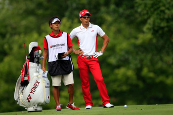 AKRON, OH - AUGUST 07:  Ryo Ishikawa of Japan (R) waits with caddie Hiroyuki Kato (L) before hitting an approach shot on the 11th hole during the final round of the World Golf Championships-Bridgestone Invitational on the South Course at Firestone Country