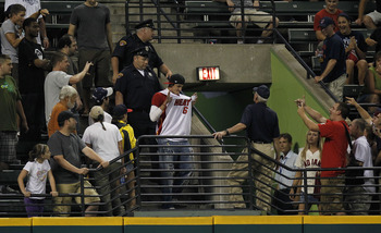 CLEVELAND - JULY 28: A fan wearing a LeBron James Miami Heat jersey at a Cleveland Indians game is escorted out of the ballpark by police while playing the New York Yankees on July 28, 2010 at Progressive Field in Cleveland, Ohio.  (Photo by Gregory Shamu