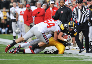 IOWA CITY, IA - NOVEMBER 20:  Tight end Allen Reisner #82 of the University of Iowa Hawkeyes is tackled by defensive tackle John Simon #54 of the Ohio State Buckeyes during the first half of play at Kinnick Stadium on November 20, 2010 in Iowa City, Iowa.