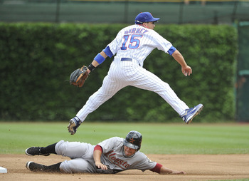 CHICAGO, IL - JULY 22:  Darwin Barney #15 of the Chicago Cubs leaps over Jose Altuve #27 of the Houston Astros after throwing to first base to complete a double play on a ground ball hit by Hunter Pence during the first inning at Wrigley Field on July 22,