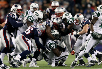 FOXBORO, MA - DECEMBER 06:  Shonn Greene #23 of the New York Jets is tackled by the New England Patriots defense at Gillette Stadium on December 6, 2010 in Foxboro, Massachusetts. The Patriots won 45-3. (Photo by Elsa/Getty Images)
