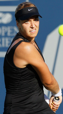 CARLSBAD, CA - AUGUST 05:  Sabine Lisicki of Germany returns a backhand to Vera Zvonareva of Russia during the Mercury Insurance Open presented by Tri-City Medical at the La Costa Resort and Spa on August 5, 2011 in Carlsbad, California.  (Photo by Jeff G