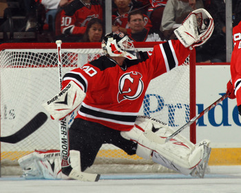 NEWARK, NJ - MARCH 30: Martin Brodeur #30 of the New Jersey Devils comes up with the puck during the second period against the New York Islanders at the Prudential Center on March 30, 2011 in Newark, New Jersey.  (Photo by Bruce Bennett/Getty Images)