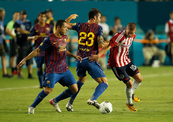 MIAMI GARDENS, FL - AUGUST 03:  Alberto Medina #10 of CD Guadalajara fights for the ball with Armando Lozano #23 during a game against FC Barcelona during the 2011 World Football Challenge at Sun Life Stadium on August 3, 2011 in Miami Gardens, Florida.