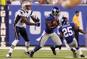 EAST RUTHERFORD, NJ - SEPTEMBER 02:  Antrel Rolle #26 of the New York Giants intercepts a pass intended for Randy Moss #81 of the New England Patriots during the first quarter on September 2, 2010 at the New Meadowlands Stadium in East Rutherford, New Jer