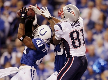 INDIANAPOLIS - NOVEMBER 15:  Antoine Bethea #41 of the Indianapolis Colts makes an interception in the endzone next to Tim Jennings #23 and Randy Moss #81 of the New England Patriots during the third quarter at Lucas Oil Stadium on November 15, 2009 in In