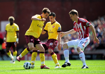 STOKE ON TRENT, ENGLAND - MAY 08:  Aaron Ramsey (L) and Robin Van Persie (C) of Arsenal combine to keep the ball away from Ryan Shawcross (R) of Stoke during the Barclays Premier League match between Stoke City and Arsenal at the Britannia Stadium on May
