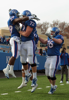 LAWRENCE, KS - NOVEMBER 20:  Running back James Sims #29 of the Kansas Jayhawks is congratulated by teammates after scoring a touchdown during the game against the Oklahoma State Cowboys on November 20, 2010 at Memorial Stadium in Lawrence, Kansas.  (Phot