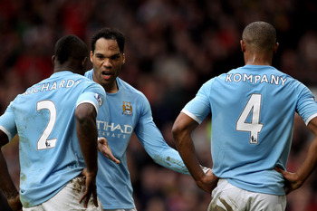 MANCHESTER, ENGLAND - FEBRUARY 12:  Joleon Lescott (C) of Manchester City has words with teammates Micah Richards (L) and Vincent Kompany (R) during the Barclays Premier League match between Manchester United and Manchester City at Old Trafford on Februar