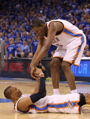 OKLAHOMA CITY, OK - MAY 23:  Kevin Durant #35 helps up teammate Russell Westbrook #0 of the Oklahoma City Thunder in the first half while taking on the Dallas Mavericks in Game Four of the Western Conference Finals during the 2011 NBA Playoffs at Oklahoma