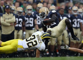 SOUTH BEND, IN - SEPTEMBER 11: Cierre Wood #20 of the Notre Dame Fighting Irish is tackled by Jordan Kovacs #32 of the Michigan Wolverines at Notre Dame Stadium on September 11, 2010 in South Bend, Indiana. Michigan defeated Notre Dame 28-24. (Photo by Jo