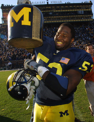 10 Nov 2001: Shantee Orr #53 of the University of Michigan Wolverines holds up 'The Little Brown Jug' after Michigan beat the MInnesota Golden Gophers 31-10  at Michigan Stadium (The Big House) in Ann Arbor, Michigan. The Little Brown Jug is one of the mo