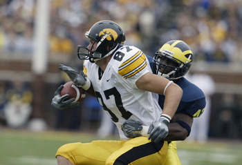 ANN ARBOR, MI - SEPTEMBER 25:  Scott Chandler #87 of the Iowa Hawkeyes runs after catching a short pass against Lawrence Reid #42 of the Michigan Wolverines during the game at Michigan Stadium on September 25, 2004 in Ann Arbor, Michigan.  Michigan defeat