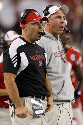 ARLINGTON, TX - DECEMBER 04:  Head coach Bo Pelini (R) of the Nebraska Cornhuskers and defensive coordinator Carl Pelini lead their team against the Oklahoma Sooners at Cowboys Stadium on December 4, 2010 in Arlington, Texas. The Sooners beat the Cornhusk