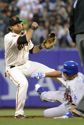 SAN FRANCISCO, CA - JULY 18: Brandon Crawford #35 of the San Francisco Giants gets his throw off to complete a double play while avoiding the slide of Juan Rivera #33 of the Los Angeles Dodgers in the fourth inning during an MLB baseball game at AT&T Park