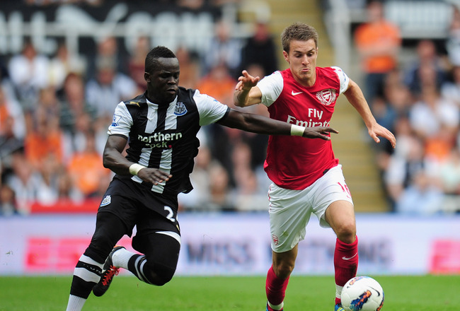 NEWCASTLE UPON TYNE, ENGLAND - AUGUST 13: Aaron Ramsey of Arsenal battles for the ball with Cheik Tiote of Newcastle United during the Barclays Premier League match between Newcastle United and Arsenal at St James' Park on August 13, 2011 in Newcastle upo