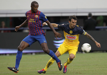 ARLINGTON, TX - AUGUST 06:  Vicente Sanchez #8 of Club America dribbles the ball against Eric Abidal #22 of FC Barcelona at Cowboys Stadium on August 6, 2011 in Arlington, Texas.  (Photo by Ronald Martinez/Getty Images)