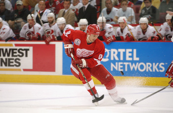RALEIGH, NC - JUNE 10:  Center Igor Larionov #8 of the Detroit Red Wings has the puck poke away from him by a Carolina Hurricanes player during game four of the NHL Stanley Cup Finals on June 10, 2002 at the Entertainment Sports Arena in Raleigh, North Ca